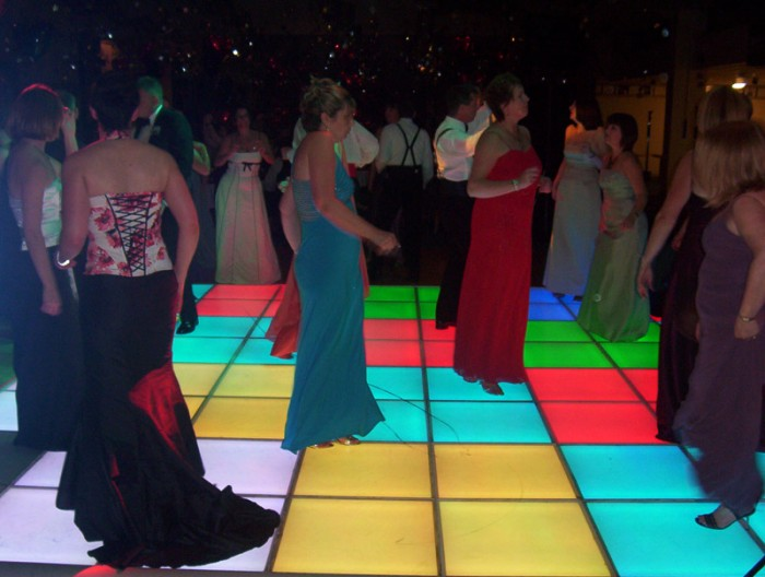 People on Colourful Light Up Dance Floor with star-cloth backdrop